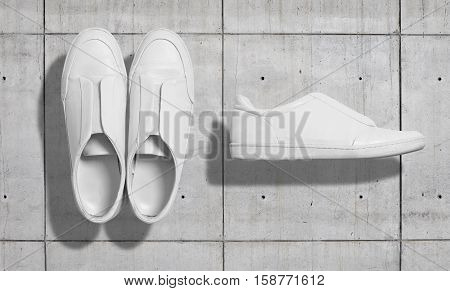 White leather sneaker like casual shoes with flat sole without shoelaces shot from the top and from the side isolated on industrial concrete wall, ready for merchandise presentation
