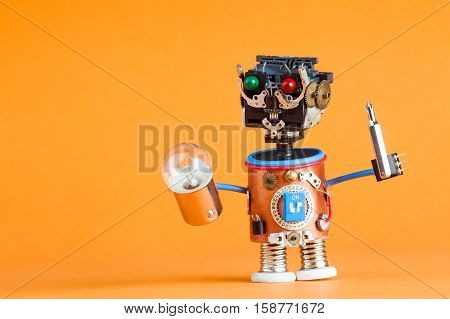 Repair service concept. Retro style robot handyman with screwdriver lamp bulb. Fun toy character. Plastic head colored green red eyes electric wire hands gears cog. Orange background