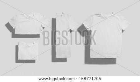 Unlabeled white shortsleeve cotton t-shirt folded in three different ways and lying flat on white background