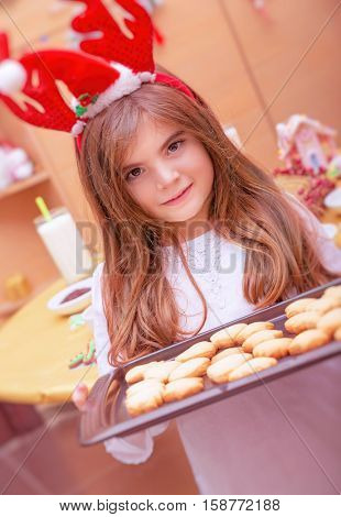 Cute small girl standing in the kitchen with dripping pan full of festive cookies, little Santa helper, traditional preparation to Christmas holidays