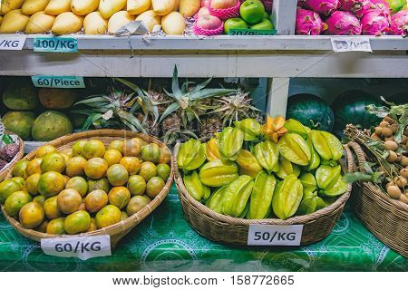 Fresh fruit market in Asia at night. Dragon fruit, carambola, mango, orange, pineapple, watermelon, longan with price tag in the bucket. Exotic street food