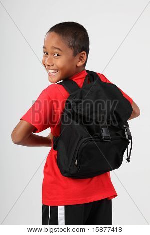 Cheerful school boy with back pack