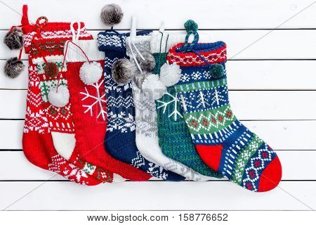 Variety Of Christmas Stockings On White Wood Table