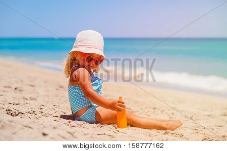 little girl applying sunblock cream on shoulder, sun protection