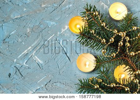 Festive Christmas background with candles and decorated with fir branches on the textured surface of the blue and gray putty. Empty space for text