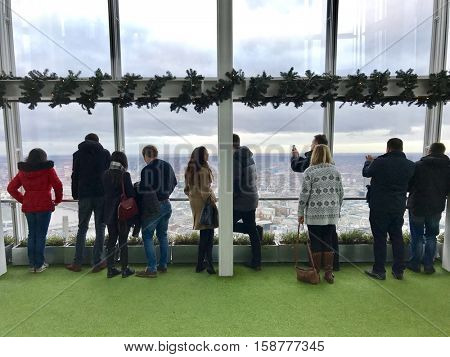 LONDON - NOVEMBER 27: People observing up to 40 miles away across the urban sprawl below from the outdoor gallery on level 72 of The View from The Shard the on November 27, 2016 in London, UK.