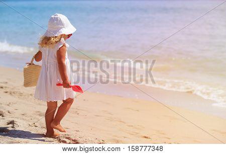little girl with beach bag walking on summer tropical beach, family beach vacation