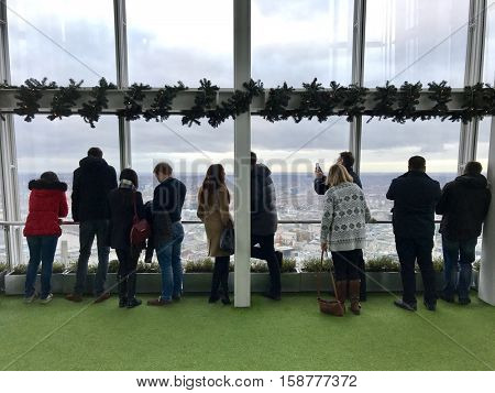 LONDON - NOVEMBER 27: People observing up to 40 miles away across the urban sprawl below from outdoor gallery on level 72 of The View from The Shard the on November 27, 2016 in London, UK.
