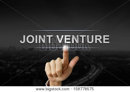 business hand clicking joint venture button on black blurred background