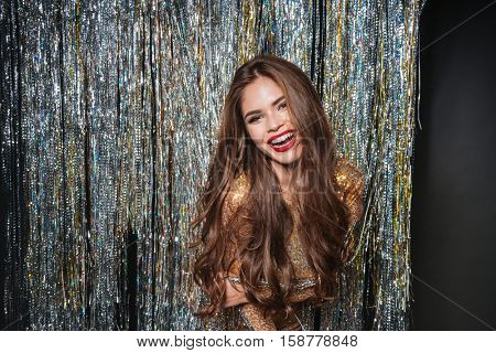 Happy attractive young woman with long hair standing and laughing over sparkling background
