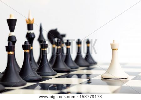 white pawn standing in front of the black pieces
