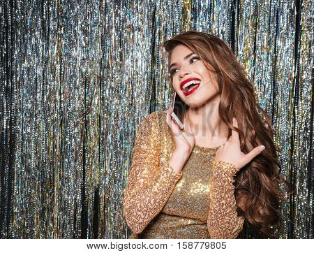 Happy cute young woman in evening dress talking on cell phone over shining background