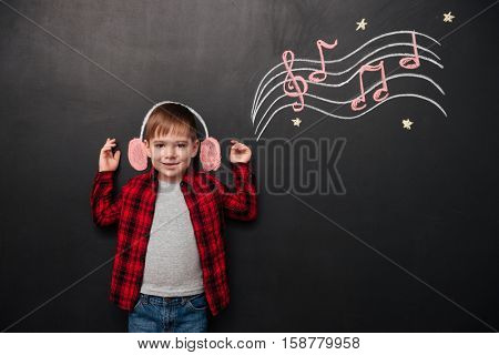 Picture of little kid listening to music over black chalk board with musically drawings