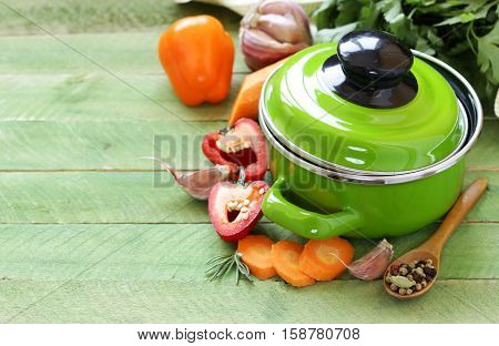 Green cooking pot and ingredients for soup or stew on rustic background