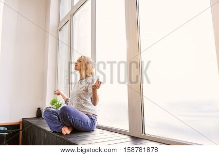 Peace and calm. Relaxed young woman is meditating at home. She is sitting in lotus position on windowsill. Her eyes are closed with serenity