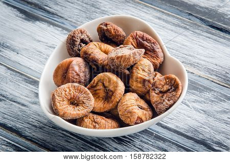 Dried figs in a white bowl on a wooden table.