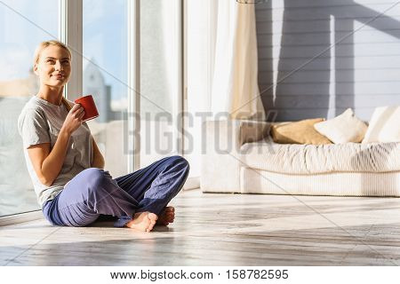 Life is great. Joyful young girl is relaxing at home. She is sitting near window and drinking coffee