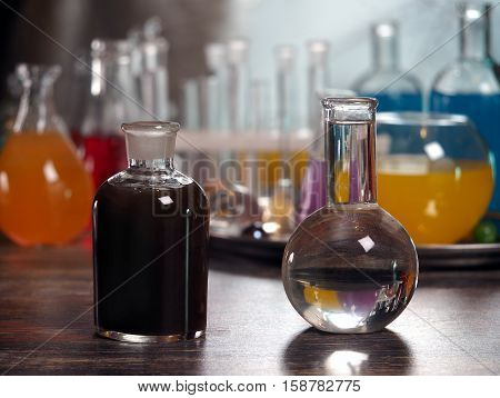 Retort with clear water and a dark bottle. Laboratory glassware with colorful liquids on the table