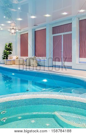 Relaxation spa zone near blue mosaic swimming pool