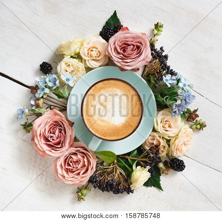 Cappuccino and flowers composition closeup. Blue coffee cup with creamy foam, fresh and dried flowers circle at white wood background, top view. Hot drinks, seasonal offer concept