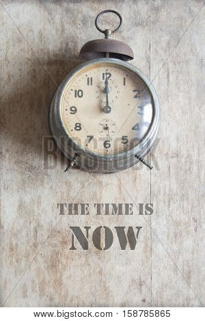 the time is now, vintage alarm clock on a brown background