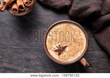 Milk tea chai latte traditional homemade refreshing morning organic healthy hot beverage drink with natural aroma spices blend in rustic clay cup on wooden table background.