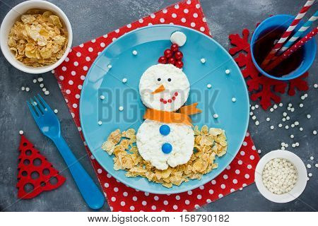Cute Christmas snowman from cottage cheese crunchy cornflakes and berries for healthy and creative breakfast for kids