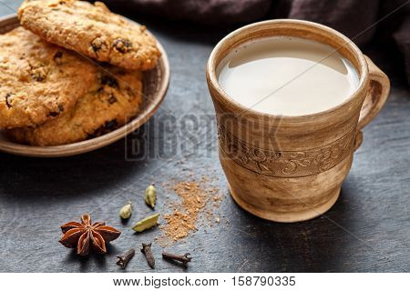 Milk tea chai latte traditional homemade refreshing morning breakfast organic healthy hot beverage drink with natural aroma spices blend, cardamon, anise, cinnamon, in rustic ceramic cup on