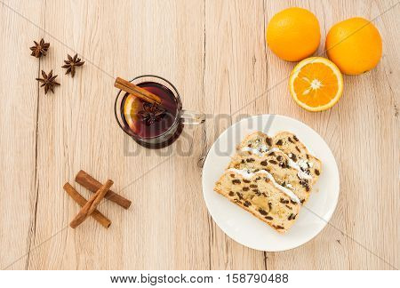 A of glass of Mulled Wine and slices of Christstollen surrounded by fresh oranges cinnamon sticks and star anise. Shot from directly above on light brown wooden background.