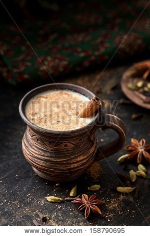 Masala pulled tea chai latte hot Indian sweet milk spiced drink, cinnamon stick, ginger, fresh spices and herbs blend, organic infusion healthy wellness beverage teatime ceremony in rustic clay cup