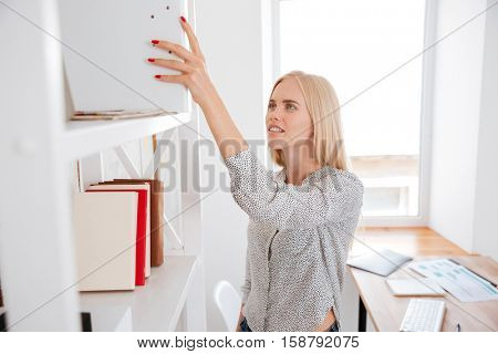 Young pretty business woman taking book from a shelf while standing in office