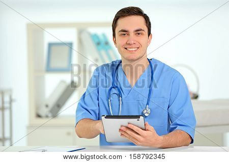 Young male doctor with tablet in office