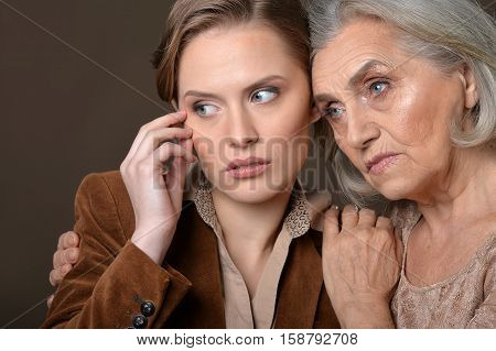 Portrait of senior and young women looking away against grey background