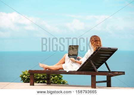 Beautiful Business Woman Working Online On Laptop Computer While Lying On Beach Lounger. Relaxing And Using Notebook For Freelance Internet Work. Communication Technology
