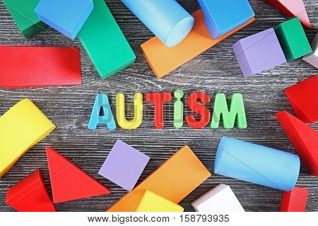 Word Autism with colorful figures on wooden background