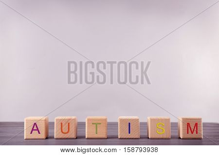 Wooden cubes with word AUTISM on light background