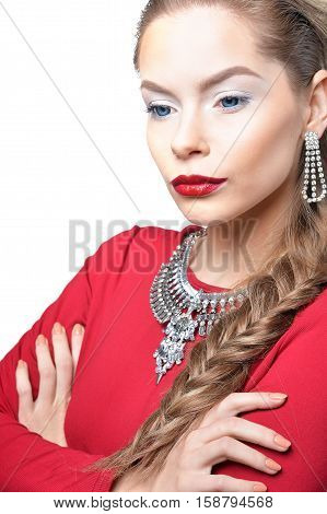 Portrait of beautiful young woman with stylish make up, elegant jewelry and in red dress with her arms crossed