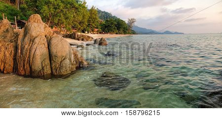 Tropical colourful sunset on the White Sand Beach, Koh Chang island, Thailand. View of dark evening sea with protruding stones