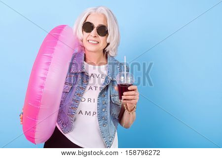 Summer time mood. Charming pleasant senior woman smiling and holding cocktail and ring lifebuoy while standing against isolated blue background.