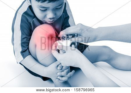 Sad asian boy looking wound his leg with red spot sore area. Nurse provides first aid on white background. Sport injury and health care concept. Studio shot.