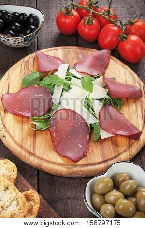 Charcuterie board with italian bresaola cured beef, grana padano cheese and rocket salad poster