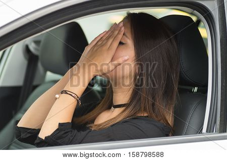 Closeup young woman sitting in car interacting upset frustrated, covering face in hands, as seen from outside drivers window, female driver concept.