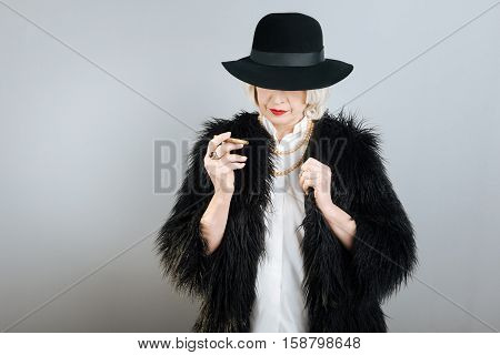 Bohemian life. Concentrated charming senior woman shutting eyes by hat and holding cigarette while standing against isolated gray background.