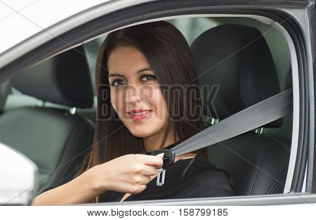 Closeup young woman sitting in car putting on seatbelt, as seen from outside drivers window, female driver concept.