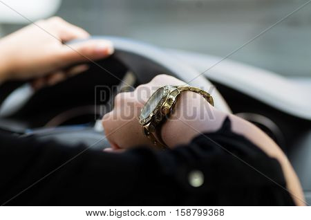 Closeup inside vehicle of woman's hand holding onto steering wheel, other arm showing off wrist watch, female driver concept.