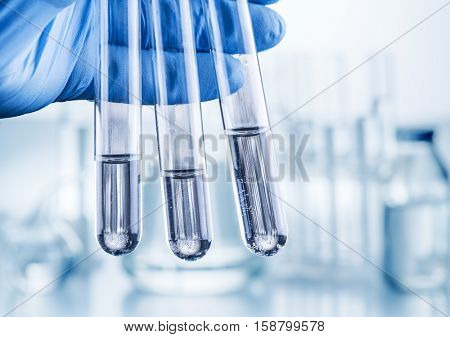 Laboratory beakers in analyst's hand in plastic gloves.