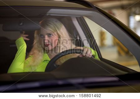 Young blonde woman sits in car and looks in rear view mirror at underground parking.