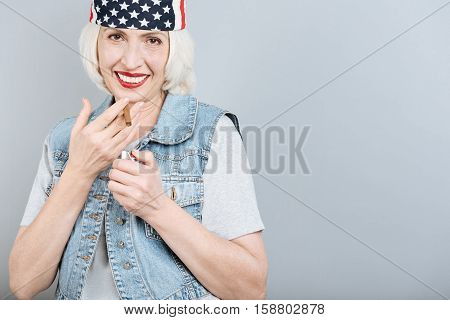 Pleasant smoking. Charming senior pretty woman smiling and smoking while standing against isolated gray background.