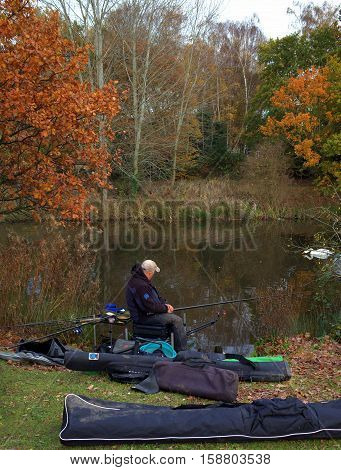 Bracknell,England - November 23, 2016: Person fishing with rod and reel on the banks of a public lake on a cloudy November day in Bracknell, England