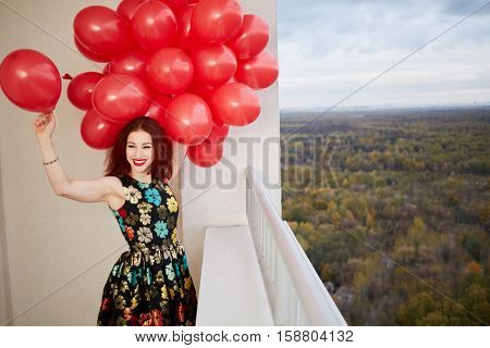 Young smiling red-haired woman holds in hand bunch of red balloons standing at balcony of highrise building.